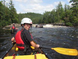 Older camper in a canoe near a waterfall.