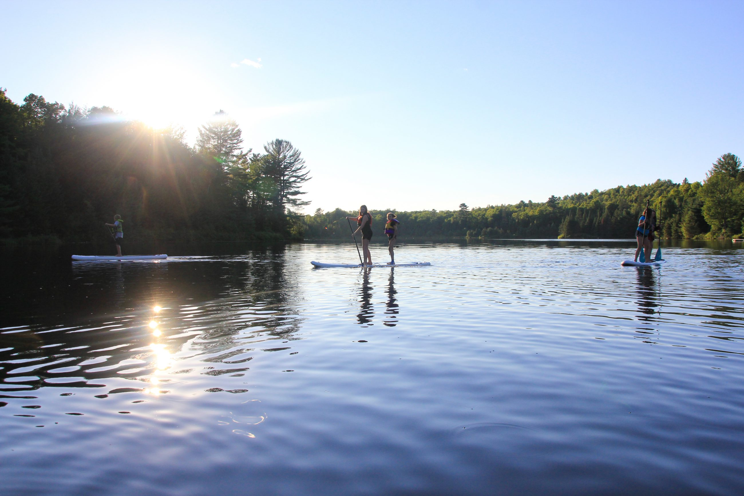 Campers out on a SUP board on calm water.