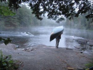 Camper portaging a canoe around rocks.