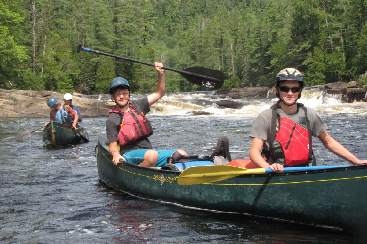 Campers in a canoe celebrating after running a set of rapids.